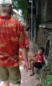 A child begging on the street. Perhaps a profession? His mother sits in front of Ed walking.